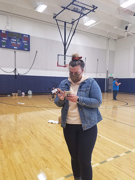 student flying a drone