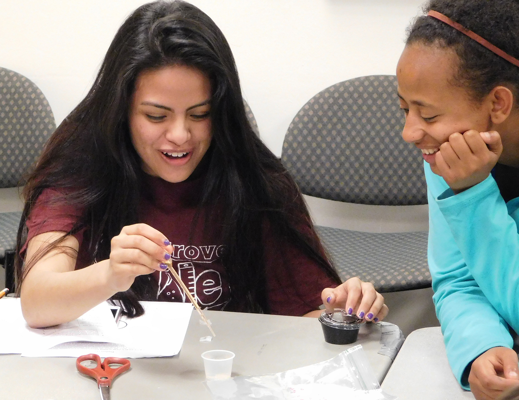 Two high school girls testing bioplastic film for presence of starch