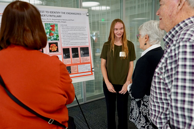Kirsten Jones (center) (undergraduate in Botany) explains her Beginning Research poster to Lurlyn and Jack Long (right)