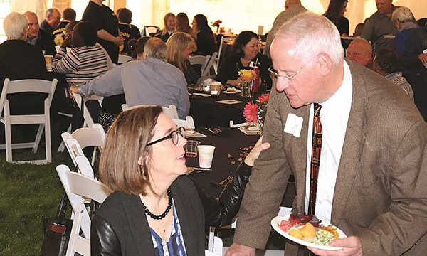 Oregon Gov. Kate Brown visits with OSU President Ed Ray at the Harvest Dinner in Aurora.