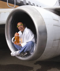 man sitting in a jet plane holding biofuel
