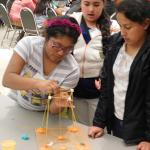 Two middle school girls building structures at Challenge event