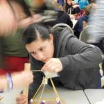 Middle school girl carefully building tower at Challenge event