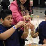 OSU student mentor advises middle school boy as he builds structure.