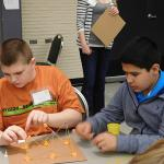 Two middle school boys work together building at Challenge event