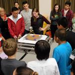 A crowd of students, mentors and staff gather to watch tower on earthquake shaker table