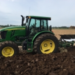 6120E tractor with plow