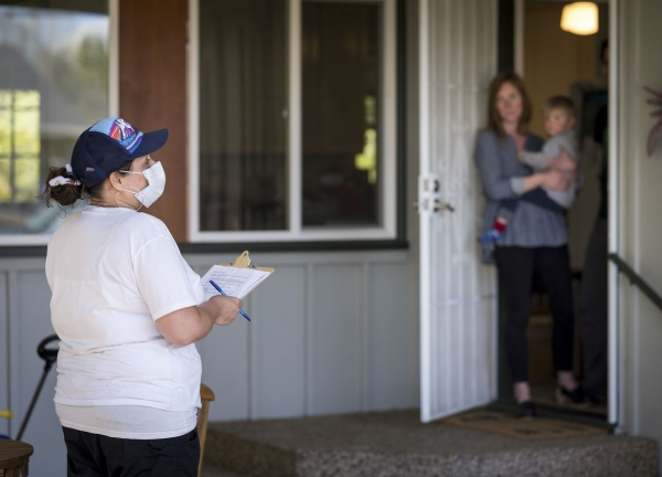 Member of OSU coronavirus testing project speaking to a resident in Corvallis