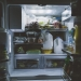 Open refrigerator with many food items stuffed inside. Light is on inside refrigerator