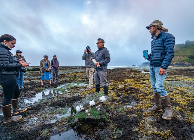 Francis Chan, center, at Otter Creek Marine Reserve. An ocean sensor is seen on the rocks. Photo credit: Oregon State University.