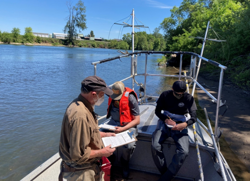 """Researchers and crew aboard """"Sparky,"""" the OSU Fisheries & Wildlife research vessel, filing out data sheets containing fish community and habitat information."""