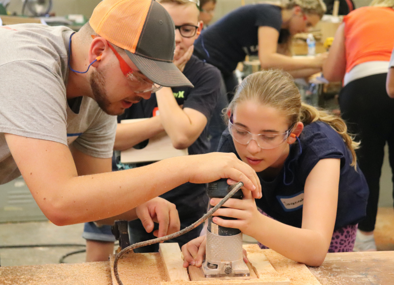 Joseph O'Brien, Tillamook County Extension Intern, assisting at the Nuts, Bolts, and Thinamajigs, Camp, which encourages students to explore trade professions.